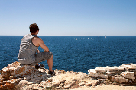 he: Man is watching the boats sailing on the sea. Background is the blue sky and the sea.