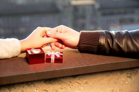 Valentines Day. Hands of couple and open red box with golden heart in it as a gift for Valentine Day.