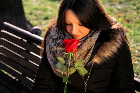 Mooi meisje ruikt rode roos en geniet van de geur. Stockfoto - 80175212