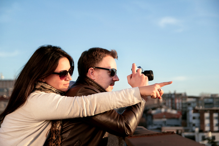 Couple taking pictures of the sunset on the rooftop. Couple enjoys the sun on the roof, the young girl showed the guy what to photograph. Reklamní fotografie