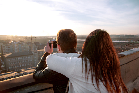 wanderlust: Couple taking pictures of the sunset on the rooftop of the city. Couple enjoys the sun on the roof and a young man photographing panorama of the city. Stock Photo
