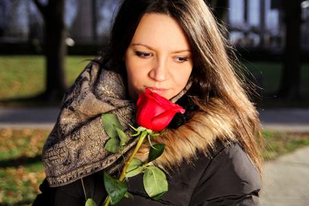 Vrolijk meisje ruikt roodrood en geniet van de geur. Stockfoto