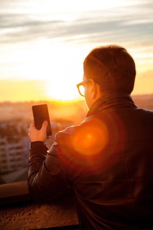 drinks after work: The guy standing on the roof, using smartphone and taking photos of the city skyline. Man wearing leather jacket and sunglasses using smart phone on the rooftop.