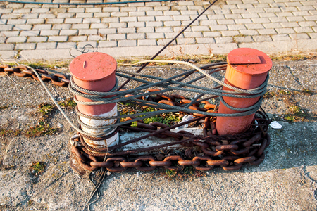 fasten: Brown cleat for ships boats. Old Knecht: steam cabinet with common ground on the docks of metal rusty brown burgundy, on the cabinet metal heavy chain to bind the ships on a background of the river.