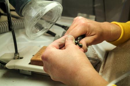 technologist: Dentures and dentistry. Dental prosthesis, dentures, prosthetics work. Dental technician in pricess of making dentures. Hands of dental technician processing metal oral prosthesis. Stomatology.
