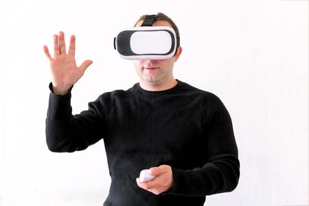 simulator: Man using a virtual glasses on white background. Young male business executive using virtual reality headset in office. Gays at office and using virtual reality glasses.