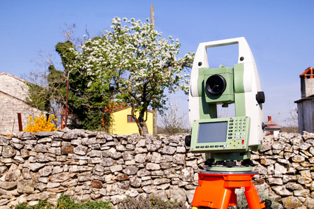 Total station. Survey Instrument geodetic device, total station set in the field. Total station surveying and measuring engineering equipment at work in garden.