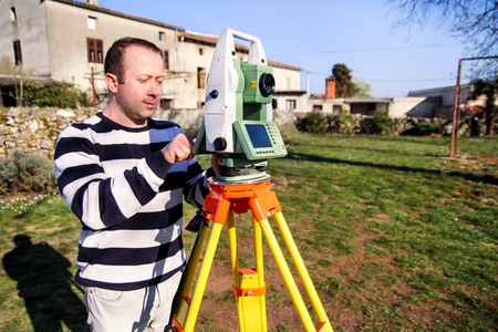 Man using of total station. Guy surveyor at work. Survey Instrument geodetic device, total station set in the field. Surveyor worker making measurement in the garden.