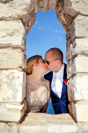 Wedding. Happy couple day wedding. Beautiful bride and groom at the beach. Cheerful married couple standing and kissing on the stone wall window. Wedding couple staying over beautiful landscape.
