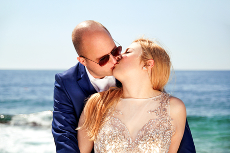 Wedding. Happy couple day wedding. Beautiful bride and groom at the beach. Cheerful married couple standing and kissing by the sea. Wedding couple staying over beautiful landscape. Stock Photo
