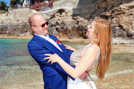 Wedding. Happy couple day wedding. Beautiful bride and groom at the beach. Cheerful married couple standing and smiling by the sea. Wedding couple staying over beautiful landscape.