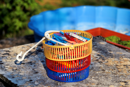 attached: Clothespins. Colorful clothespin in the basket, stand on the table in the garden. Cloth clothespins.
