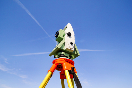 exact position: Total station with blue sky in the background. Survey Instrument geodetic device, total station set in the field. Total station surveying and measuring engineering equipment at workplace.