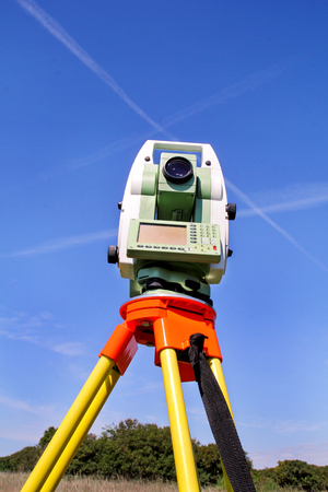 Total station with blue sky in the background. Survey Instrument geodetic device, total station set in the field. Total station surveying and measuring engineering equipment at workplace.