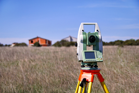 Total station. Survey Instrument geodetic device. Fall time land surveying, set in field. Modern surveyor equipment, used in surveying and building construction for measurement, at construction site.