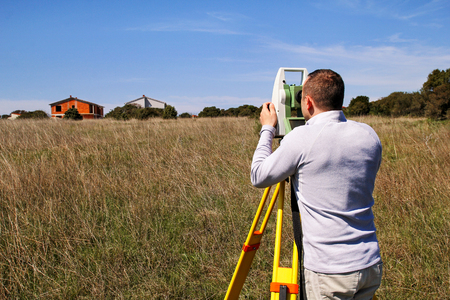 Man using of total station. Guy surveyor at work. Survey Instrument geodetic device, total station set and surveyor worker making measurement in the field. Total station outdoor at construction site.
