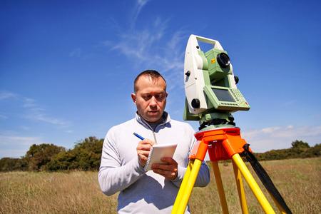 Hombre topógrafo en el trabajo y el uso de la estación total. Encuesta Instrumento dispositivo geodésico, conjunto de estación total y el trabajador topógrafo haciendo la medición en el campo. Estación total al aire libre en el sitio de construcción.