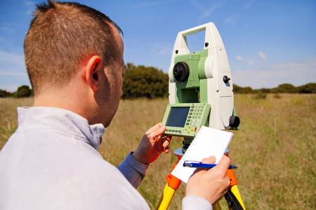 男測量作業とトータル ステーションの使用します。調査計測器測地デバイス、トータル ステーションのセットと測量ワーカー分野で測定を行います 写真素材
