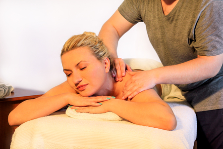 resting: Massage relax studio. Beautiful young woman relaxing with hand relaxing massage at beauty spa center. Smiling girl enjoys on massage table. Massage therapist massaging with neck muscles. Body care.
