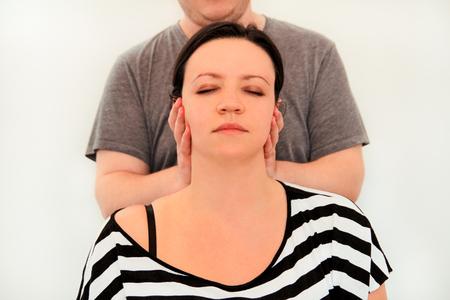 마사지 휴식 스튜디오. 여자는 물리 치료사에 의해 마사지 그녀의 목에. 목 근육을 마사지하는 마사지 치료사. 바디 케어. 아름 다운 젊은 여자 손으로