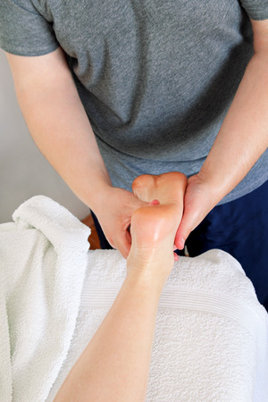 Foot massage in beauty salon, close up view. Woman having sports foot massage in spa salon. Male masseur therapist hands doing on female foot massage. Professional masseuse massaging foot of girl.