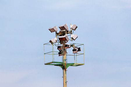 street lamp: Stadium floodlight tower with reflectors with blue sky. Lighting pole tower at the sports stadium and ground. Big lamp and light stadium poles or sports lighting. Flood light pole in the spotlight.