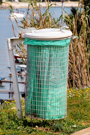 Recycling industry. Recycle bin on the grass with white frame. A green wate bin in a city natural outdoor on a sunny day, toward the sea and seaside. Trash can  and dustbin with a lot of garbage.