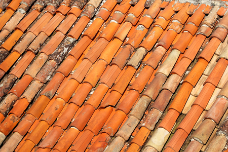 Part of tile on the roof of a house building, closeup. A red tiled terracotta roof. The orange roof tiles, maps and textures. Texture of tiles. Background with part of roof. Rows of roof bricks. Stock Photo