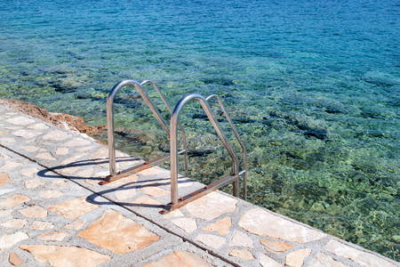 Handrail swimming on the beach of the sea. Steel handrail, swimming, blue sea, seaside, waves, summer, travel, natural environment, Mediterranean, Adriatic sea. The entry to the sea with handrail.