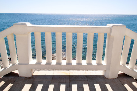 Sea and fence with white balusters and blue sky. Beautiful Seascape with white Balcony. White terrace by the blue sea. Summer view with classic white balustrade and empty terrace overlooking the sea.