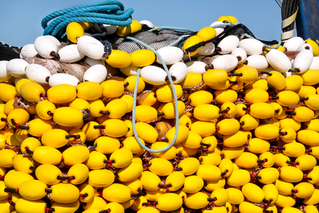cable tangle: Yellow floats on the pile, covering fishing nets on the blue boat in the summer sun, close up. Fishing floats with rope knot netting piled in a fishing boat. Stock Photo