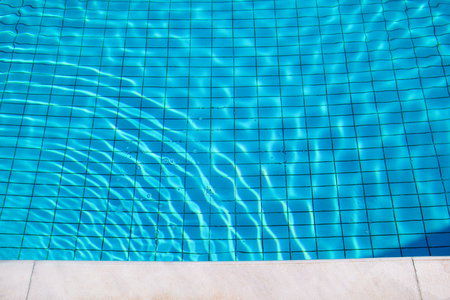 Blue ripped water in swimming pool. Swimming pool bottom caustics ripple and flow with waves background. Clear light blue pool water ripples with sun reflections. Surface of blue swimming pool.
