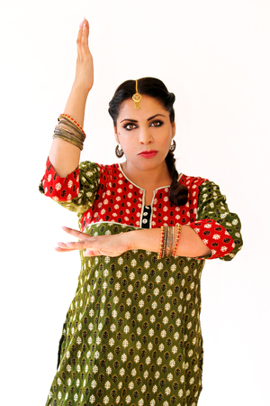 Woman dancing Indian dance in national dress. A beautiful girl portrait in shree kurta patiala set style, horn for the Indian dance movement. Indian dancer in traditional clothing. Bollywood dance. Stock Photo