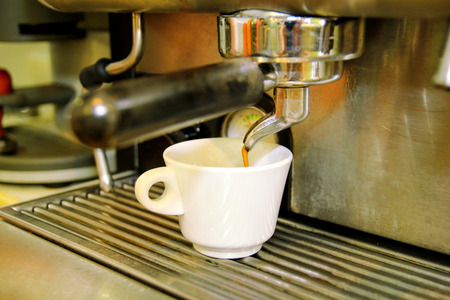 appliance: Coffee maker. Close-up white coffee cup. Espresso machine. A professional coffee maker in a cafe. The coffee pours into the cup from the appliance. Cappuccino, macchiato, espresso coffee. Hot drink.