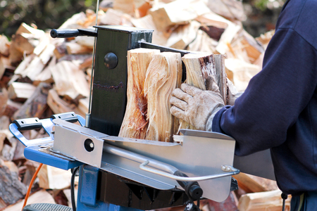 Saw cutting wood for winter. A man cutting firewood for the winter using a modern machine lumber saw. Wood industry. Heating season, winter season. Renewable resource of energy. Environmental concept.
