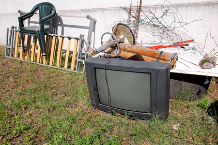 古いテレビセット、かさばるゴミの残りの部分。昔のテレビは、混合のゴミの山が付いている壁の横に捨て。自然な環境で。リサイクル業界。エコ 写真素材