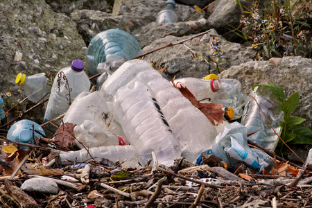 Plastic and glass bottles thrown away and left in nature, pile of garbage. Ecological, ecology, recycling industry, not ecology, recycled material, pollution, neglect, environmental protection. Banco de Imagens