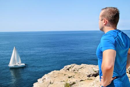 Hombre guapo vistiendo ropa deportiva toma un descanso después de un entrenamiento de carrera y disfruta de un hermoso entorno natural, con vistas al horizonte del mar Adriático, un velero navegando en el fondo. Foto de archivo