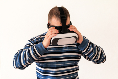 Man wearing and playing mobile game app on device virtual reality glasses on white background. Man action and using in virtual headset, VR box for use with smart phone. Contemporary technology concept Stock Photo