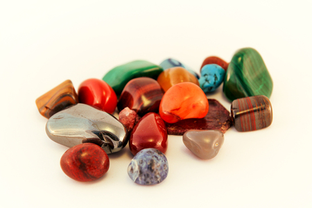 Semi precious stones / Crystal Stone Types / healing stones, worry stones, palm stones, ponder stones / Various stones gemstones background texture / Heap of various colored gems mineral collection. Foto de archivo