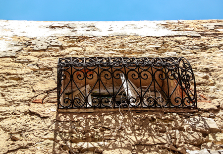 View of detail of stone building with typical Mediterranean arabic style window and balcony with ornament old forging in Medina of Tunis, Tunisia  Tunisian window decorations  A blue sky background. Stock Photo