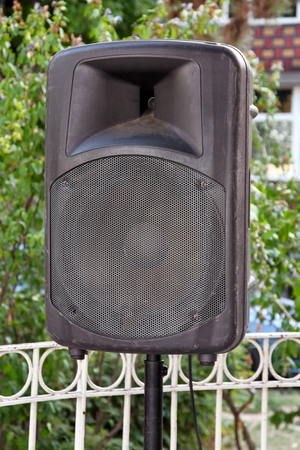 Black big speaker on stand outdoor  A big p.a. speaker on a stage at an outdoor music festival  Large audio speaker and equipment  Urban city street music concept.