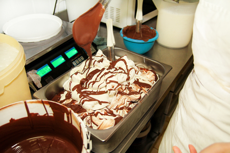 Woman working at ice cream factory is decorations of creamy vanilla ice cream with chocolate dressing in steel container. Pouring chocolate in the tray with frozen ice cream. Beautiful dessert, sweet.