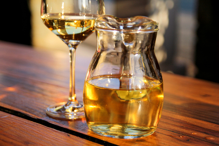 Bottle of white wine and glass on wooden table top. Glass of chilled white wine on table near the beach, in a restaurant tavern. Stock Photo