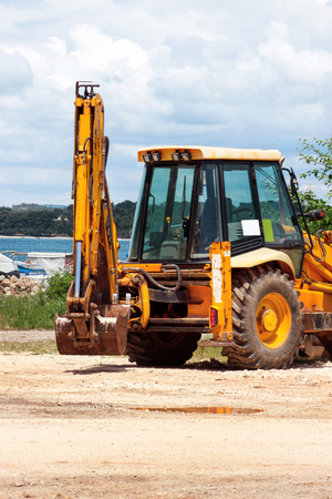 Yellow excavator, bulldozer machine and worker tractor. Road works. Road machinery at construction site. Road company and building machines for construction. Industry, renovation and infrastructure.