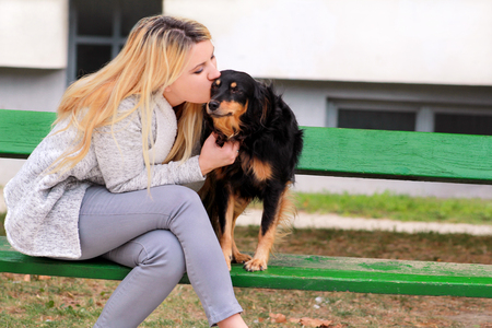 Beautiful woman with his small mixed breed dog sitting and posing in front of camera on wooden bench at city park