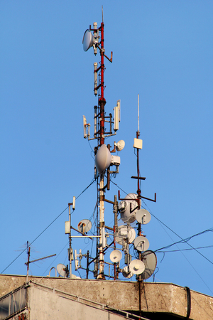 Telecommunication base stations network repeaters on the roof of building. Stock Photo