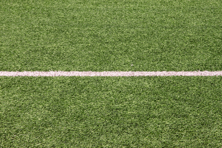 Part of sport soccer stadium and artificial turf football field. Detail, close up of green grass with white lines, goal line, corner line. Focus football field selected background, texture, wallpaper. 스톡 콘텐츠