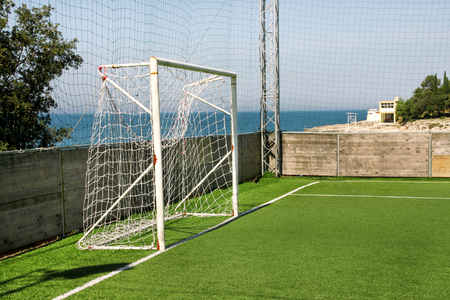 Soccer goal door with white net. Football goal at soccer field with green grass and sport stadium on campus, bleachers, white line and soccer field corner. Sports elements, equipment and environment.