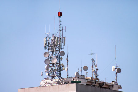 Telecommunication base stations network repeaters on the roof of building. The cellular communication aerial on city building roof. Cell phone telecommunication tower. Antennas on top of building. 스톡 콘텐츠